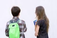 Los estudiantes de los adolescentes de la muchacha y del muchacho hablan el uno al otro Visión trasera, trasera Fotos de archivo libres de regalías