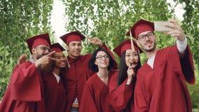 Los estudiantes de graduación alegres de los amigos están tomando el selfie con smartphone, gente joven son presentación, mostran almacen de video