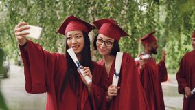 Los estudiantes de graduación bonitos de las muchachas están tomando el selfie con las volutas del diploma usando smartphone, las almacen de metraje de vídeo