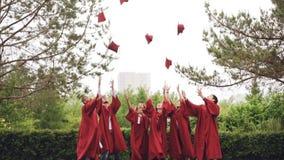 Los estudiantes de graduación descuidados están lanzando birretes en el aire después que los coge, riendo y aplaudiendo las manos metrajes