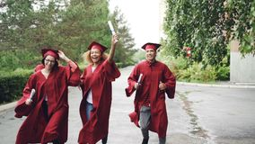 Los estudiantes de graduación emocionados están corriendo con los diplomas en los vestidos que llevan del territorio del campus y almacen de metraje de vídeo