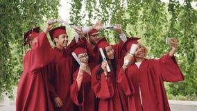 Los estudiantes de graduación emocionados están tomando el selfie con smartphone, gente joven están agitando los diplomas, presen metrajes