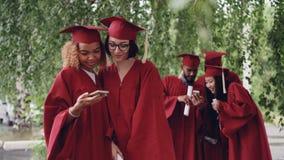 Los estudiantes de graduación hermosos de las mujeres jovenes están tomando el selfie con smartphone entonces que miran las fotog metrajes