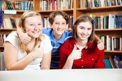 Los estudiantes de la biblioteca dan los pulgares para arriba Imágenes de archivo libres de regalías
