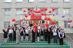 Los estudiantes de la escuela lanzan los globos en el cielo Fotos de archivo