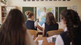 Los estudiantes de la escuela secundaria estudian el globo durante la lección de la geografía almacen de metraje de vídeo