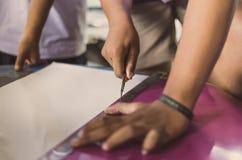 Los estudiantes de la High School secundaria están cortando impresiones y etiquetas engomadas usando el cuchillo imagen de archivo