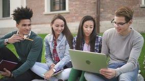Los estudiantes de la raza mixta miran a través del ordenador portátil que miran en la información de la pantalla en línea almacen de metraje de vídeo