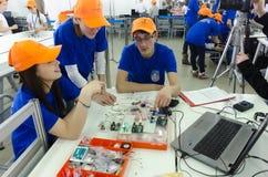 Los estudiantes de la universidad muestran componentes electrónicos Foto de archivo