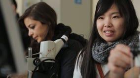 Los estudiantes de mujeres indios y asiáticos asisten a un entrenamiento práctico con los microscopios ópticos metrajes