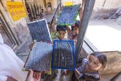 Los estudiantes de un pueblo indio enseñan orgulloso el presente sus pizarras Imagen de archivo libre de regalías