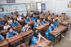 Los estudiantes del muchacho y del girl scout se sientan en la sala de clase Fotografía de archivo libre de regalías