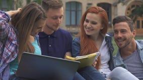Los estudiantes discuten algo en el césped en campus almacen de metraje de vídeo
