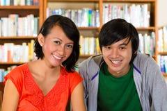 Los estudiantes en biblioteca son un grupo de aprendizaje Foto de archivo libre de regalías