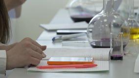 Los estudiantes en el trabajo en el laboratorio de la química toman notas en un cuaderno Alumno femenino que usa el teléfono en l almacen de video