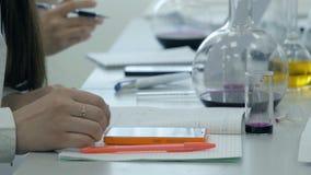 Los estudiantes en el trabajo en el laboratorio de la química toman notas en un cuaderno Alumno femenino que usa el teléfono en l fotos de archivo libres de regalías
