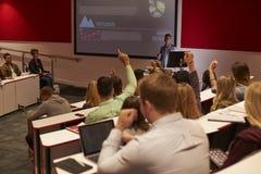 Los estudiantes en la conferencia de la universidad aumentan las manos para hacer preguntas imagenes de archivo