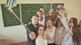 Los estudiantes en la sala de clase hacen graciosamente el selfie en el fondo del consejo escolar almacen de video