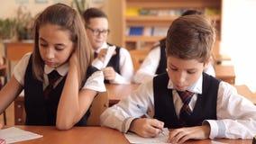Los estudiantes escriben en la lección metrajes