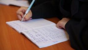 Los estudiantes escriben en un cuaderno metrajes