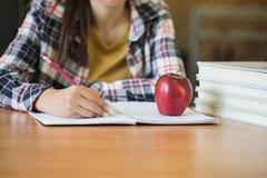Los estudiantes escriben los libros en la biblioteca, concepto de la educación fotografía de archivo