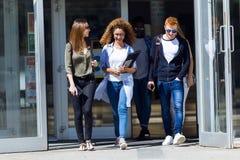 Los estudiantes están caminando en pasillo de la universidad durante rotura y están comunicando Fotografía de archivo libre de regalías