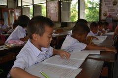 Los estudiantes están escribiendo en sitio de clase Imagen de archivo libre de regalías
