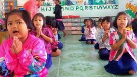 Los estudiantes están recitando las palabras que serán buenos niños