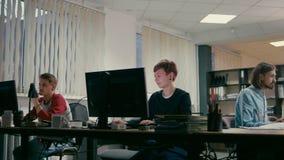 Los estudiantes están trabajando en sus proyectos juntos en los ordenadores en la oficina metrajes