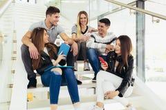 Los estudiantes est?n estudiando en biblioteca La gente joven est? pasando el tiempo junto Libro de lectura y rato de comunicaci? foto de archivo libre de regalías