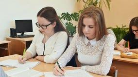 Los estudiantes estudian en la sala de clase en el escritorio de la escuela Foto de archivo