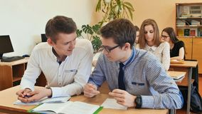 Los estudiantes estudian en la sala de clase en el escritorio de la escuela Fotos de archivo libres de regalías
