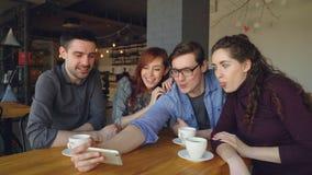 Los estudiantes felices están tomando el autorretrato del selfie en café, haciendo caras divertidas y los gestos, abrazo y risa almacen de metraje de vídeo
