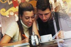 Los estudiantes felices jovenes de los pares aprenden el examen en café, visión con un w Imagenes de archivo