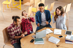 Los estudiantes felices jovenes que usan el ordenador portátil hacen gesto del ganador Foto de archivo