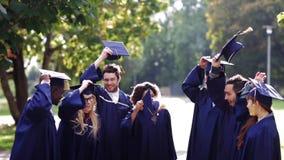 Los estudiantes felices que lanzan el mortero suben para arriba