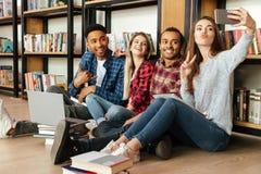 Los estudiantes felices que se sientan en biblioteca hacen el selfie por el teléfono móvil Fotos de archivo libres de regalías