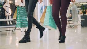Los estudiantes femeninos de los amigos están caminando en el centro comercial que sostiene las bolsas de papel en manos que disf almacen de metraje de vídeo