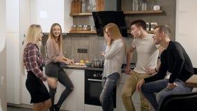 Los estudiantes femeninos y masculinos alegres están charlando en una cocina durante el partido casero, la sonrisa y la risa metrajes
