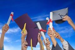 Los estudiantes gradúan con los sombreros y los diplomas Foto de archivo libre de regalías