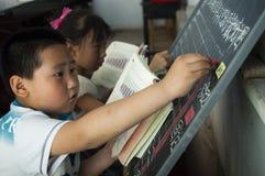 Los estudiantes hacen la matemáticas en la pizarra Imágenes de archivo libres de regalías