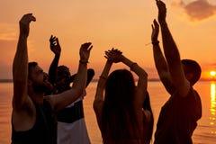 Los estudiantes jovenes extáticos que gozan de la playa van de fiesta en la puesta del sol foto de archivo libre de regalías