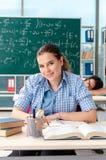 Los estudiantes jovenes que toman el examen de la matem?ticas en sala de clase foto de archivo