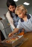 Los estudiantes jovenes toman un curso preliminar en la cocina con su profesor V Foto de archivo