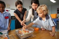 Los estudiantes jovenes toman un curso preliminar en la cocina con su profesor V Fotografía de archivo libre de regalías