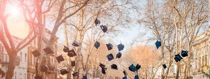 Los estudiantes lanzan para arriba sus casquillos Graduación de estudios El concepto fotografía de archivo libre de regalías