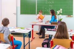 Los estudiantes leyeron a un profesor de la mujer en la pizarra Imagen de archivo