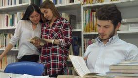 Los estudiantes masculinos leen el libro en la biblioteca imagenes de archivo