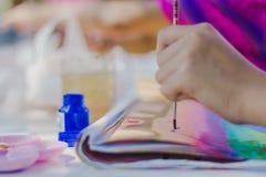 Los estudiantes practican el pintar del paisaje usando colores de cartel Foto de archivo libre de regalías