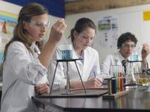 Los estudiantes que cuidan hacia fuera experimentan en laboratorio Imagenes de archivo